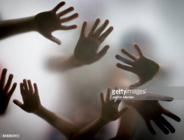many hands silhouette behind glass - violenza foto e immagini stock