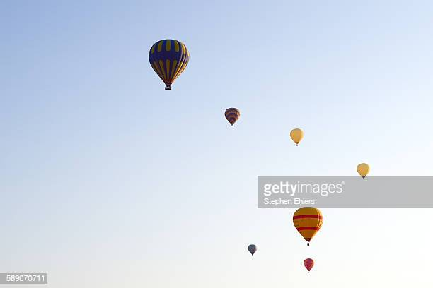 Many hot air balloons float in the clear sky, seen from another balloon.