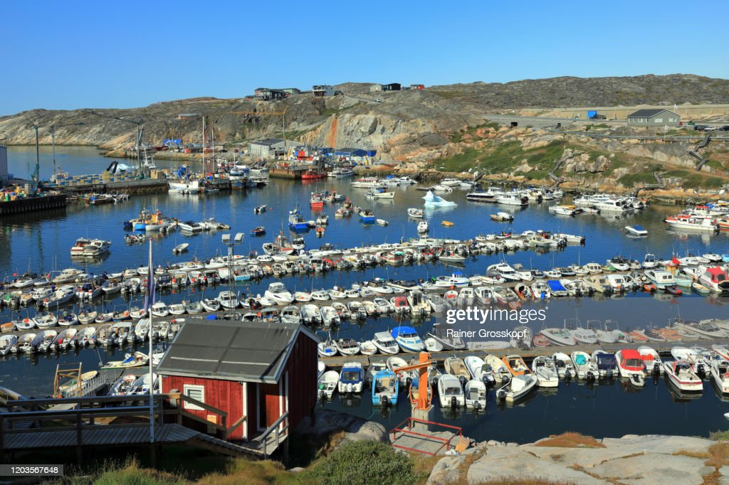 Many little boats in a small harbor with some small icebegrs swimming between the boats : Stock-Foto