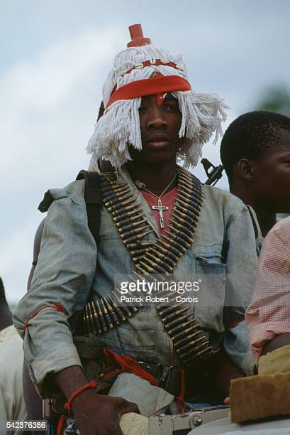 Many members of the National Patriotic Front of Liberia don unusual outfits for spiritualistic reasons or scare tactics like this young man who wears...
