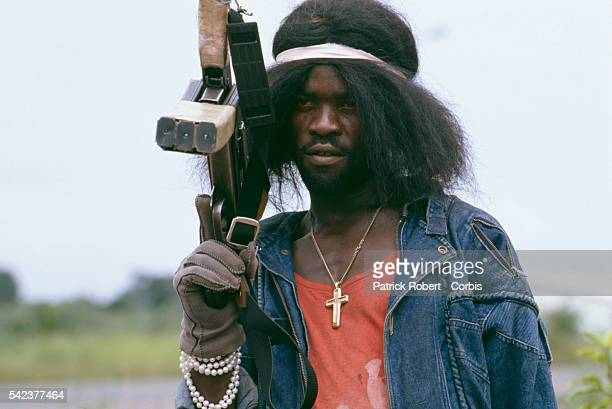 Many members of the National Patriotic Front of Liberia don unusual outfits for spiritualistic reasons or scare tactics like this man who wears a wig...