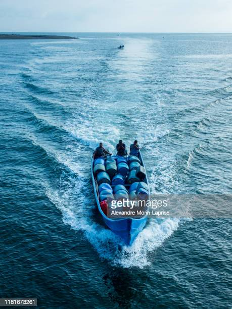 many men on blue speed boat fill with merchandise crusing in the bay - alexandre coste foto e immagini stock