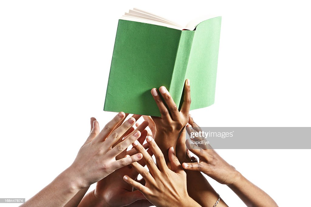Many mixed hands reach for green-covered book against white : Stock Photo