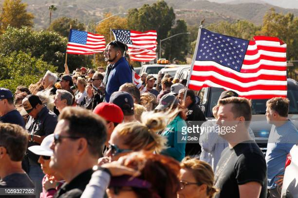 Many onlookers watch as a hearse carrying the flag draped casket in a procession for Ventura County Sheriff's Sgt Ron Helus from the Borchard Road...