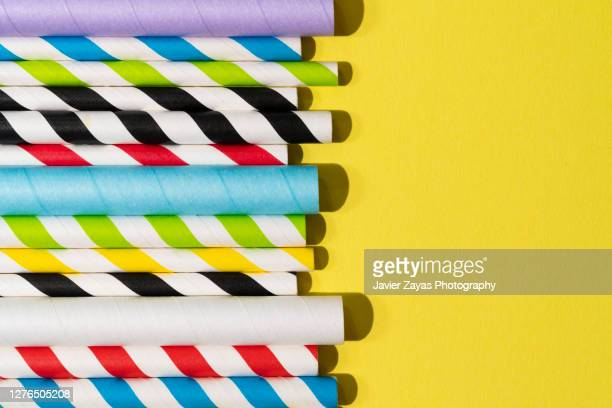 many paper drinking straws on yellow background - simple living stock pictures, royalty-free photos & images
