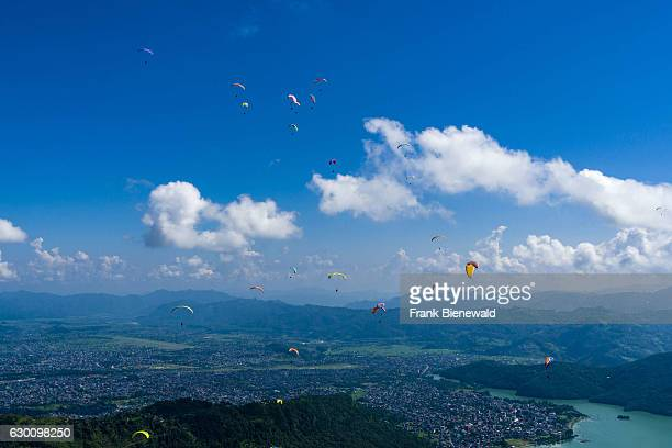 Many paragliders are flying over Pokhara and Phewa Lake