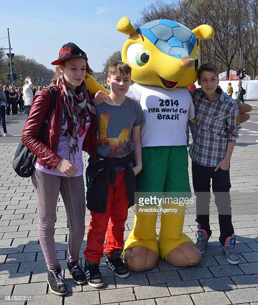 Many people pose with Fuleco during the FIFA World Cup display at the Brandenburg Gate in Berlin Germany on March 30 2014