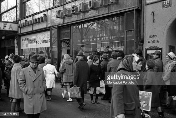 Many people queueing in front of a food shop on Christmas' Eve Prague December 1968