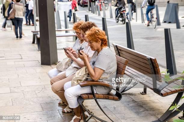 夏の日の間にブダペストにお互いのほか坐っている間多くの人々 が自分の携帯電話にテキスト メッセージ