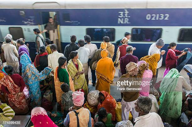 Many people waiting for delayed trains on a platform of the railway station pushing inside a arriving train