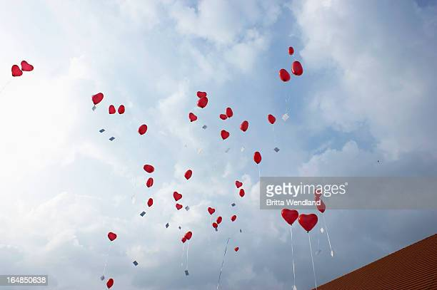 Many red heart shaped helium balloons floating up