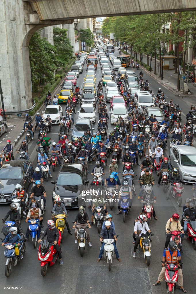 Many scooters and cars on a road in Bangkok : ストックフォト