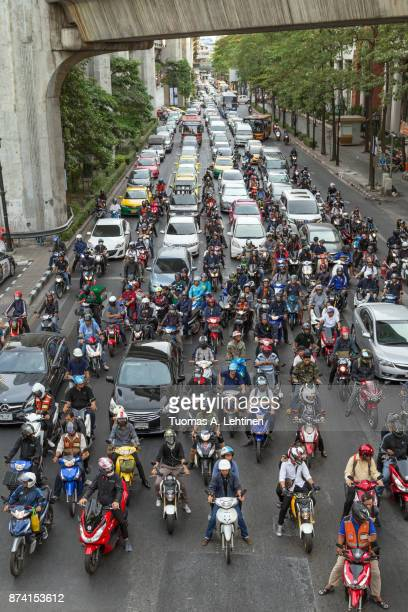 many scooters and cars on a road in bangkok - ラチャダムリ通り ストックフォトと画像