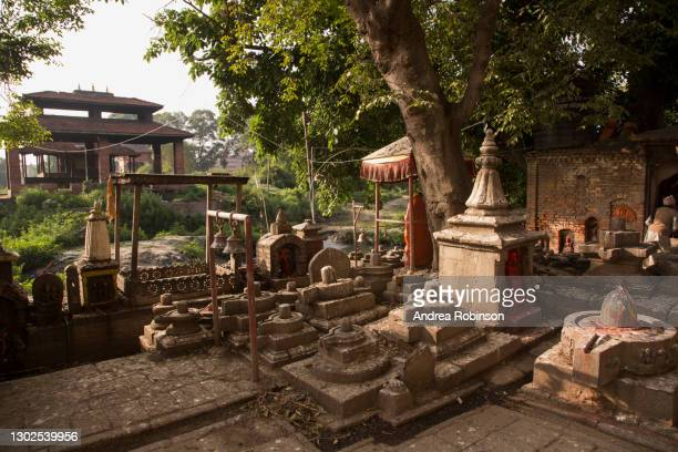 many shiva lingam's and small temples in the hindu temple area alongside the river in the hanuman ghat area of bhaktapur in the kathmandu valley, nepal. - shiva lingam stock pictures, royalty-free photos & images