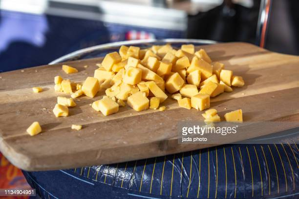 many small pieces of sliced cheese on a wooden board - cheddar cheese stock pictures, royalty-free photos & images