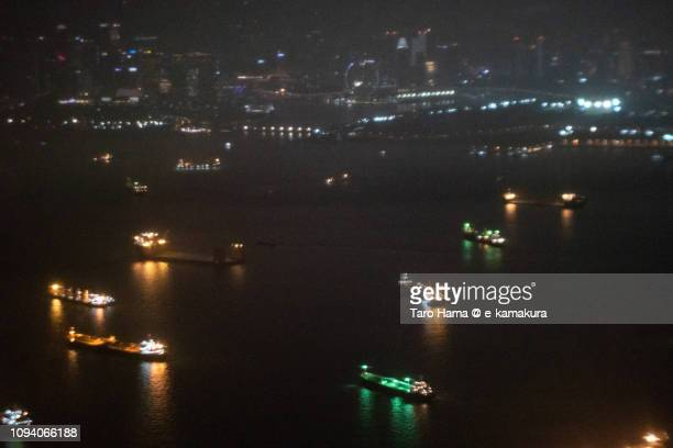 Many tankers on Singapore Strait in Singapore night time aerial view from airplane