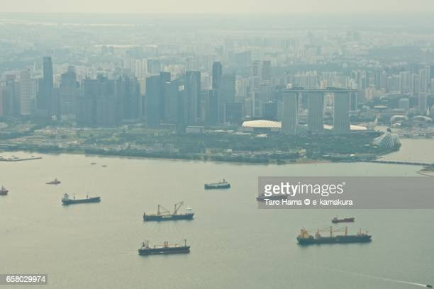 Many tankers on Singapore Straits and Singapore cityscape aerial view from airplane