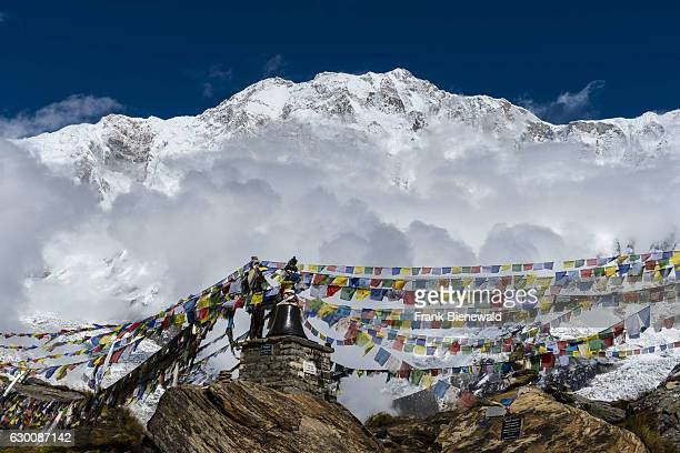 Many tibetan prayer flags are set up at a memorial for died climbers, the snow covered Annapurna 1 North Face, partly covered by monsoon clouds, in...