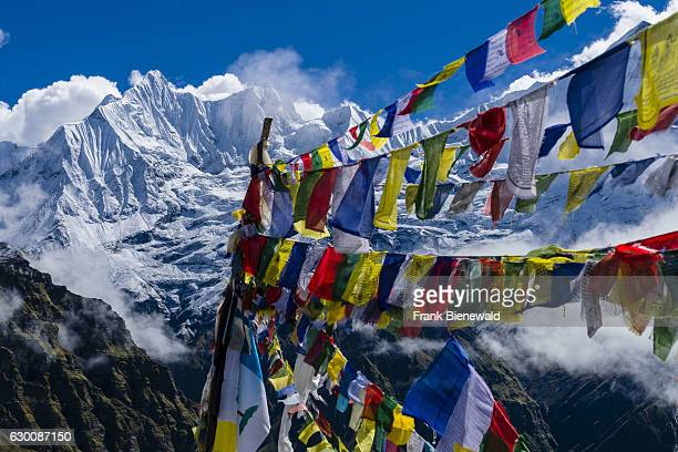 Many tibetan prayer flags are set up at a memorial for died climbers the snow covered Annapurna 1 North Face partly covered by monsoon clouds in the...