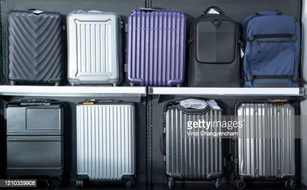many travel luggage on the shelf - businesswear stockfoto's en -beelden