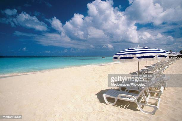 Many umbrellas and white lounge chairs in a line on Shoal Bay Beach on Anguilla, Caribbean