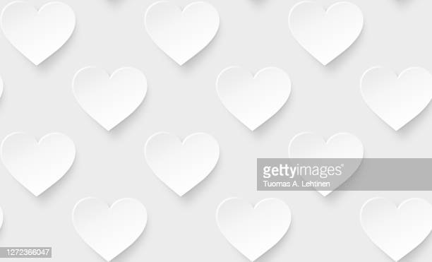many white hearts on a light gray background. - love stock pictures, royalty-free photos & images