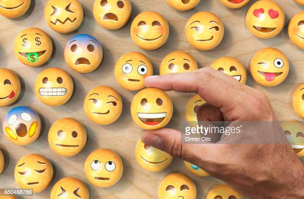 Many wooden emoticon or Emoji face balls, hand holding one