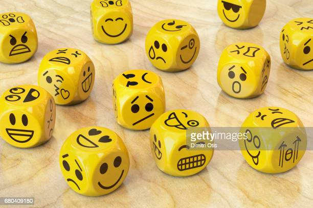 Many yellow dice with emoji or emoticon faces