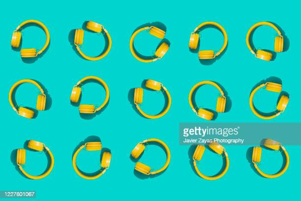 many yellow headphones on a green background - música pop fotografías e imágenes de stock