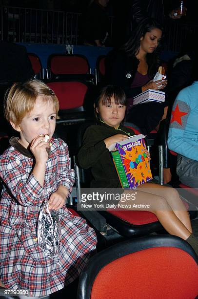 Manzie Tio and Bechet Dumaine the daughters of Woody and SoonYi Allen munch on popcorn during the Big Apple Circus' opening night gala benefit in...