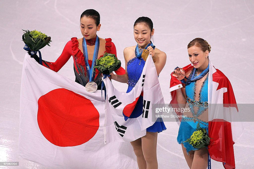 Mao Asada of Japan celebrates the silver medal, Kim Yu-Na of South Korea the gold medal and Joannie Rochette of Canada the bronze medal during the medal ceremony for the Ladies Free Skating on day 14 of the 2010 Vancouver Winter Olympics at Pacific Coliseum on February 25, 2010 in Vancouver, Canada.