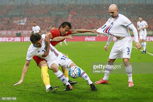 Mao Jianqing of China competes for the ball with Elmar Bjarnason and Kristinn Jonsson of Iceland during the 2017 Gree China Cup International...