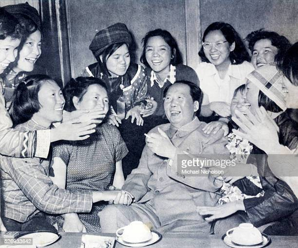 Mao Zedong Photograph from 1957 showing him laughing and surrounded by a group of deighted women some in modern and some in ethnic dress The...