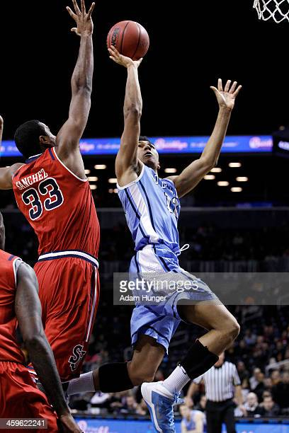 Maodo Lo of the Columbia Lions shoots over Orlando Sanchez of the St John's Red Storm during the Brooklyn Hoops Winter Festival at Barclays Center on...