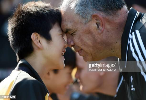 Maori All Blacks Kaumatua Luke Crawford offers a hongi a traditional Maori greeting to a boy during a Maori's traditional haka lesson in Tokyo on...