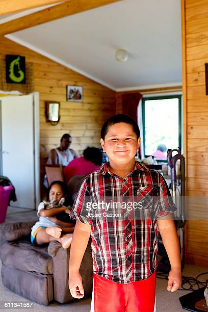 Maori boy in home with family in background