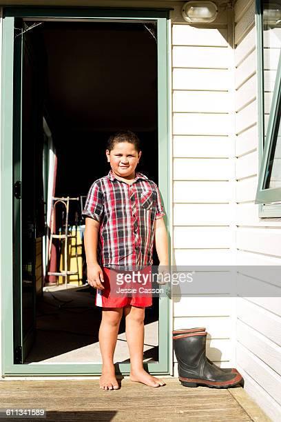 Maori boy in house doorway