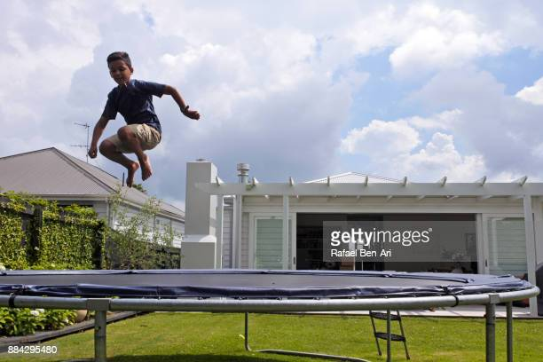maori boy jumps on trampoline in his home backyard - rafael ben ari imagens e fotografias de stock