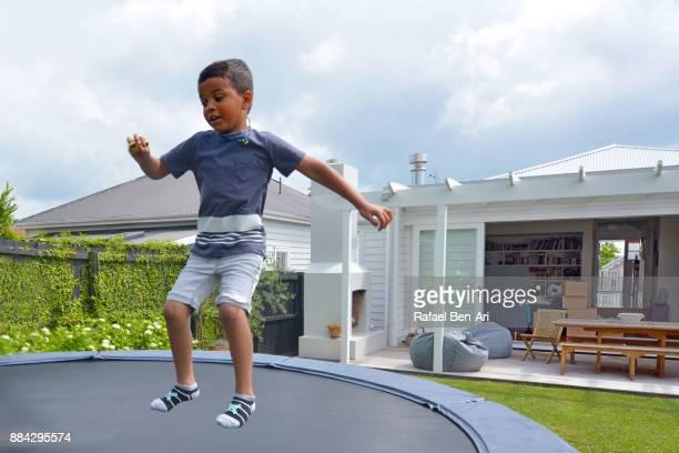 maori boy jumps on trampoline - rafael ben ari stockfoto's en -beelden