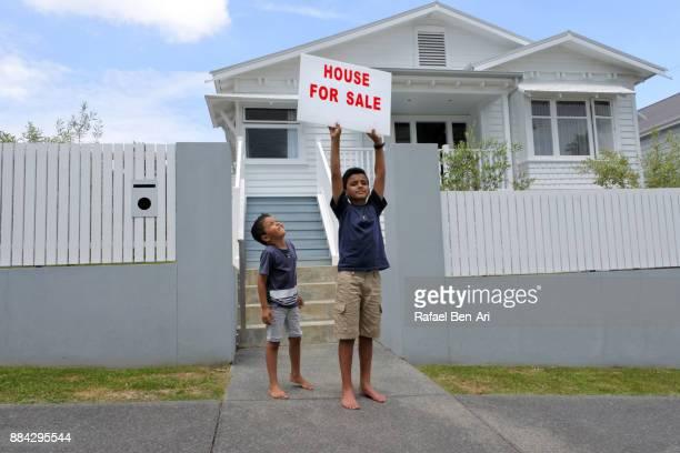 maori boys holds a home for sale sign - rafael ben ari stock-fotos und bilder