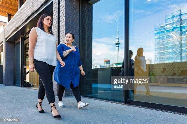 Maori Business Women Walking Together Past a Modern Office Building