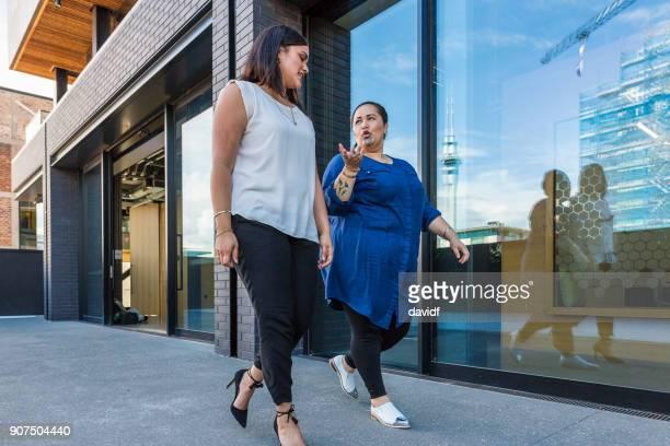 Maori Business Women Walking Together Past a Modern Office Building