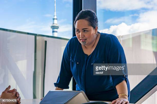 Maori Businesswoman Making a Conference Call With Auckland Skytower Behind