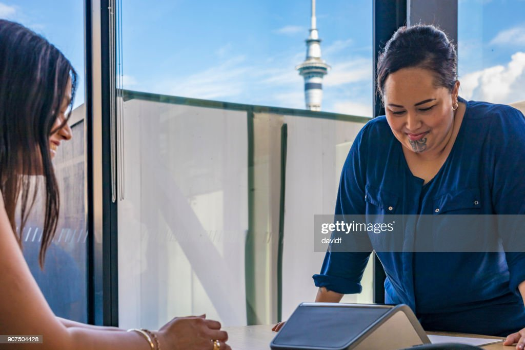 Maori Businesswoman Making a Conference Call With Auckland Skytower Behind : Stock Photo