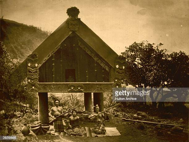 A Maori chief and his family sit outside their home a carved wooden structure built on stilts