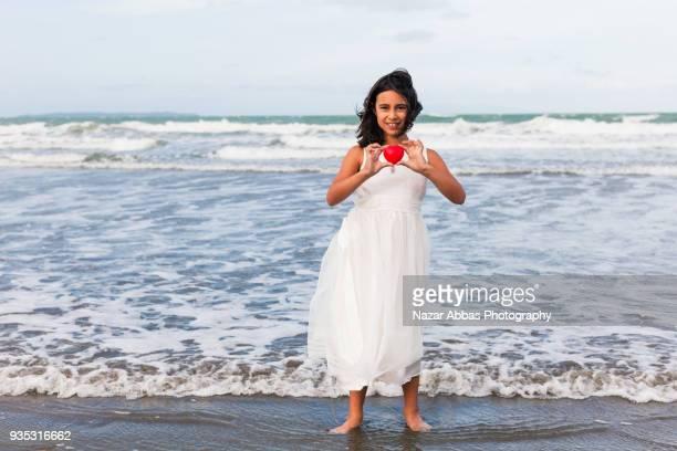 Maori girl holding heart shape in her hands.