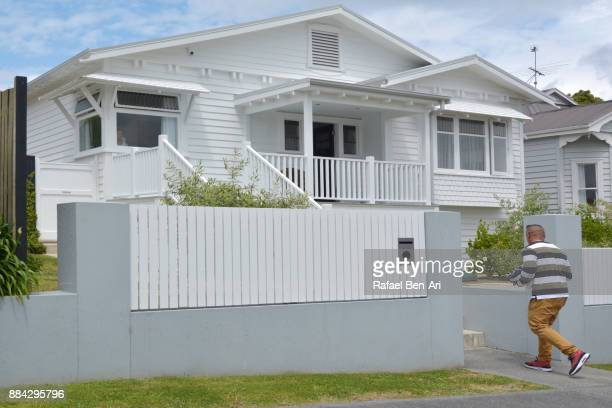 Maori man enters his traditional bungalow house