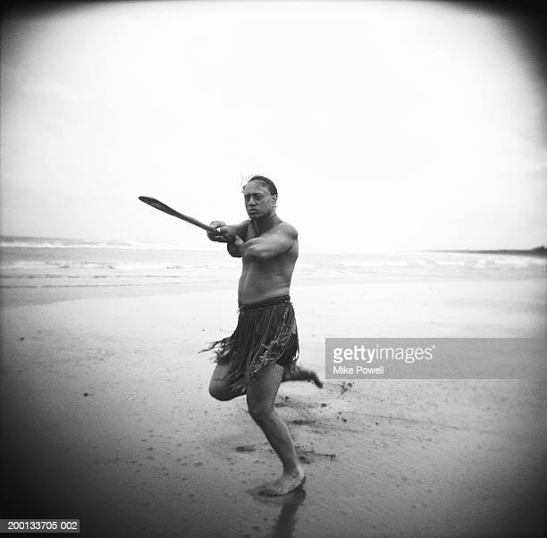 Maori man performing Haka Powhiri on beach (B&W)