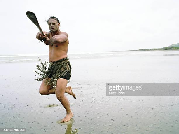 Maori man performing Haka Powhiri on beach