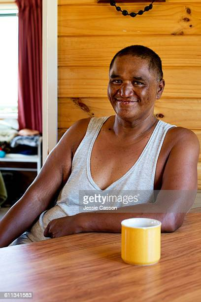Maori man sitting at table with cup